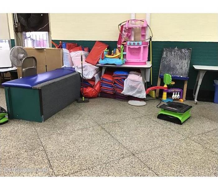 Air mover drying floor with children's' items in the background