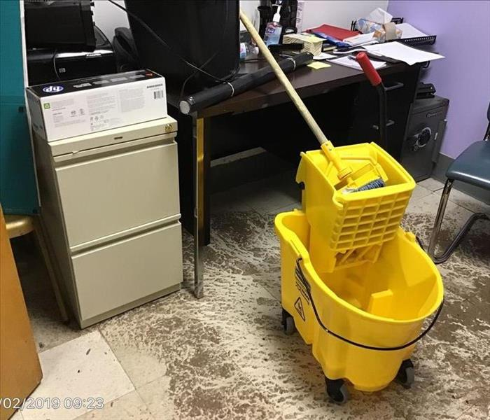 Office desk, safe, and file cabinet with dry sewage on the floor and a yellow janitorial mob and bucket.