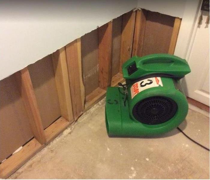 SERVPRO restoration equipment being used in corner of room; flood cuts along wall